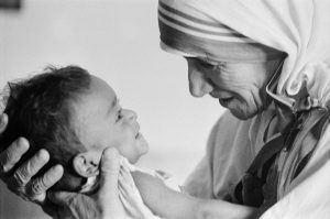 "1974, Calcutta, West Bengal, India  --- Mother Teresa with a child from the orphanage she operates in Calcutta. Mother Teresa (Agnes Gonxha Boyaxihu), the Roman Catholic-Albanian nun revered as India's ""Saint of the Slums,"" was awarded the 1979 Nobel Peace Prize.  --- Image by © Nik Wheeler/Sygma/Corbis"