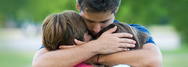 Pai e filhas se abraçam, em sinal de amor e perdão